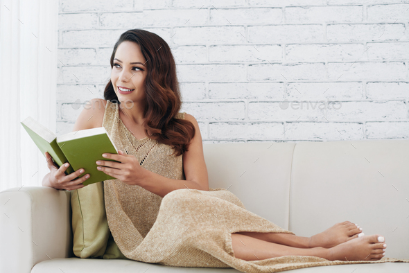 Attractive lady dreaming while reading romance book - Stock Photo - Images