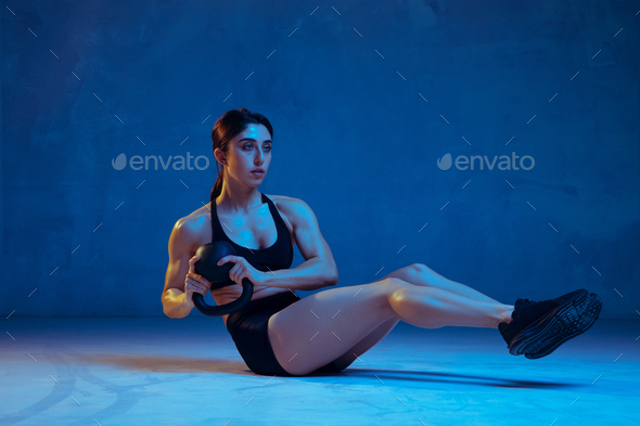 Caucasian young female athlete practicing on blue studio background in neon light - Stock Photo - Images