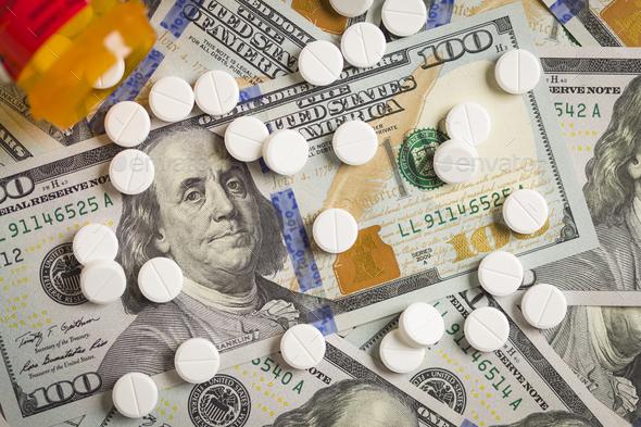 Medicine Pills Scattered on Newly Designed One Hundred Dollar Bills - Stock Photo - Images