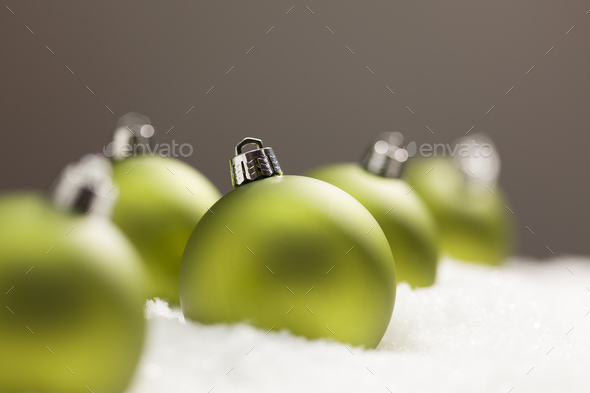 Green Christmas Ornaments on Snow Over a Grey Background - Stock Photo - Images
