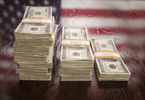 Thousands of Dollars with Reflection of American Flag on Table - Stock Photo - Images