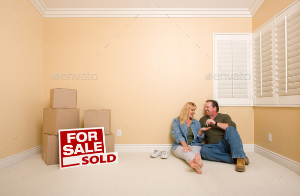 Couple on Floor Near Boxes and Sold Real Estate Signs - Stock Photo - Images