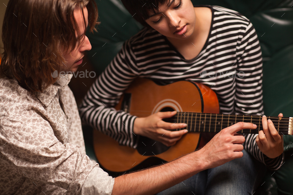 Young Musician Teaches Female Student To Play the Guitar - Stock Photo - Images
