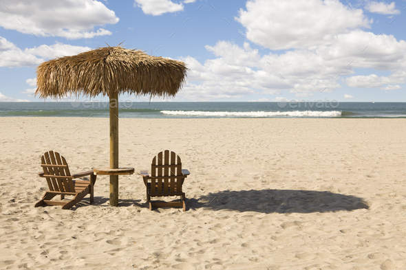 Two Beach Chairs and Umbrella on Beautiful Ocean Sand - Stock Photo - Images