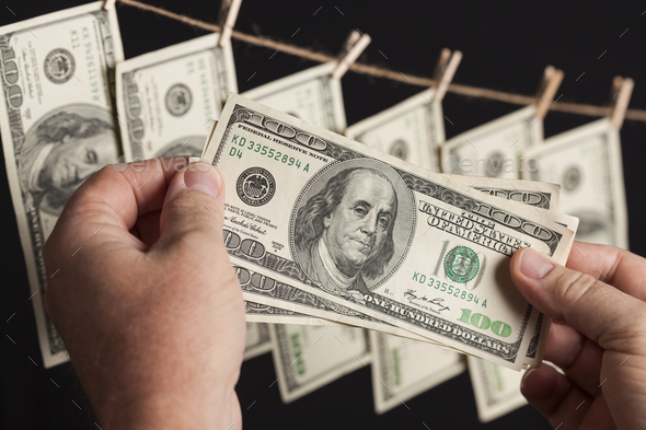 Male Holding Hundred Dollar Bills, Many Handing from Clothesline - Stock Photo - Images