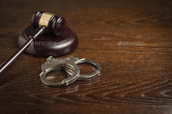 Gavel and Pair of Handcuffs on Table - Stock Photo - Images