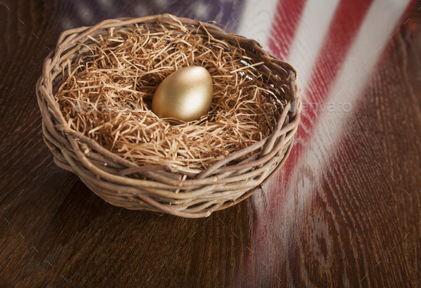 Golden Egg in Nest with American Flag Reflection on Table - Stock Photo - Images