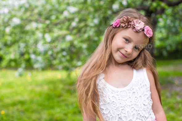 Portrait of little adorable girl in blossoming apple garden - Stock Photo - Images