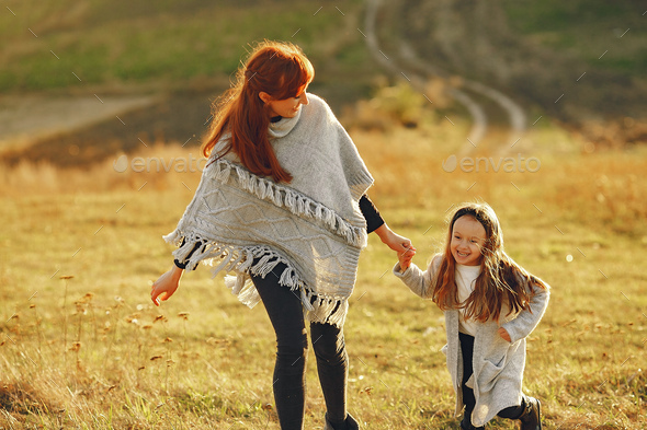 Mother with little daughter playing in a autumn field - Stock Photo - Images