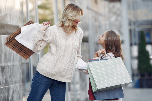 Mother with daughter with shopping bag in a city - Stock Photo - Images