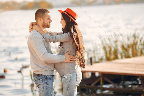 Pregnant wife with her husband standing near river - Stock Photo - Images
