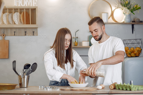 Beautiful couple prepare food in a kitchen - Stock Photo - Images
