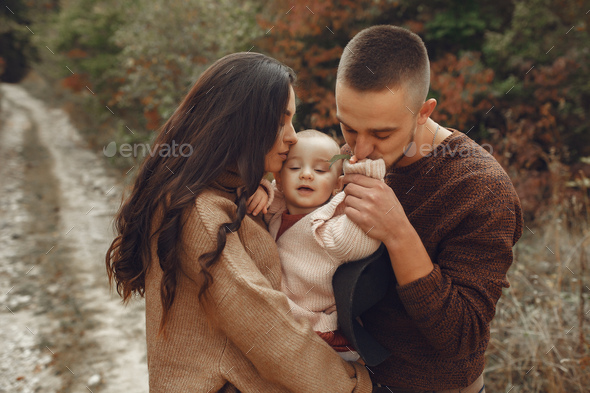 Cute and stylish family playing in a autumn field - Stock Photo - Images