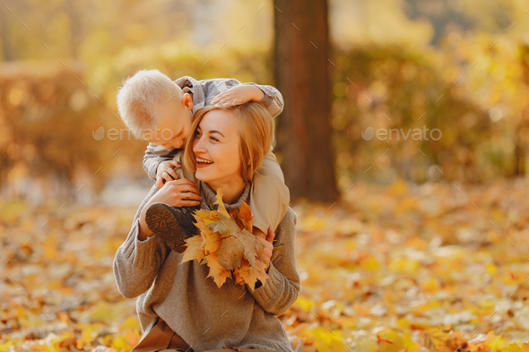 Mother with little son playing in a autumn field - Stock Photo - Images