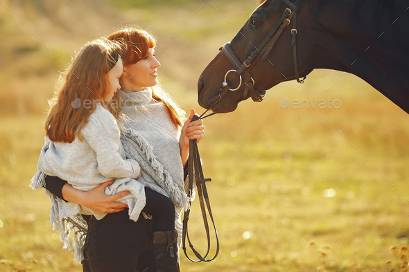 Mother and daughter in a field playing with a horse - Stock Photo - Images