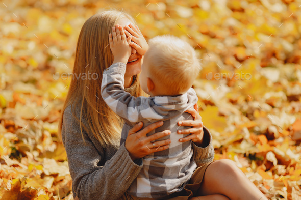 Mother with little son sitting in a autumn field - Stock Photo - Images