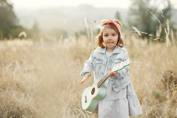 Cite little girl in a autumn park playing on a guitar - Stock Photo - Images