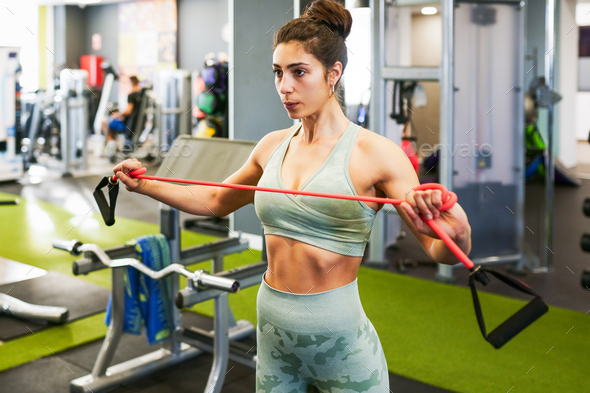Young sportswoman warming up with fitness gums in the gym - Stock Photo - Images