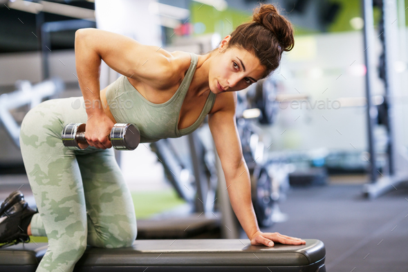 Woman working on her triceps and biceps in a gym with dumbbells - Stock Photo - Images