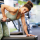 Woman working on her triceps and biceps in a gym with dumbbells - PhotoDune Item for Sale