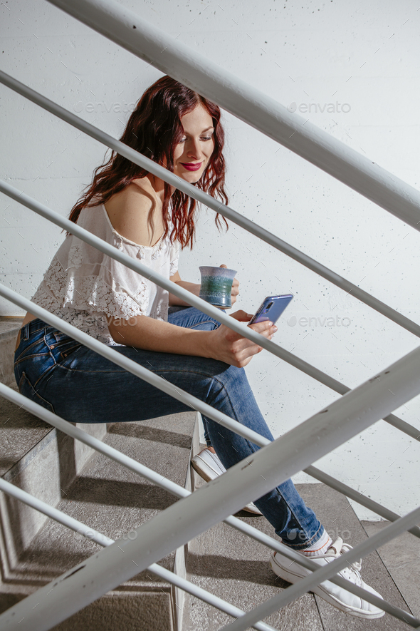 Woman sitting on stairs looking at messages on her smartphone - Stock Photo - Images