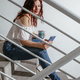 Woman sitting on stairs looking at messages on her smartphone - PhotoDune Item for Sale