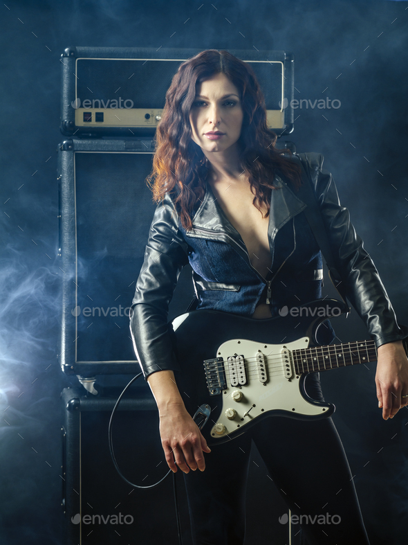 Beautiful woman with red hair holding electric guitar - Stock Photo - Images