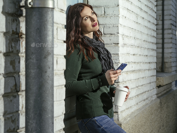 Woman checking her messages and drinking coffee outside - Stock Photo - Images