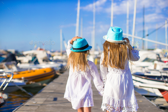 Adorable little girls walking in a port during summer vacation - Stock Photo - Images