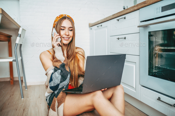 Beautiful smiling girl in knitted cardigan using mobile and working on laptop at kitchen - Stock Photo - Images