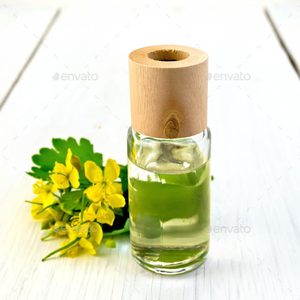 Oil with celandine on light board - Stock Photo - Images