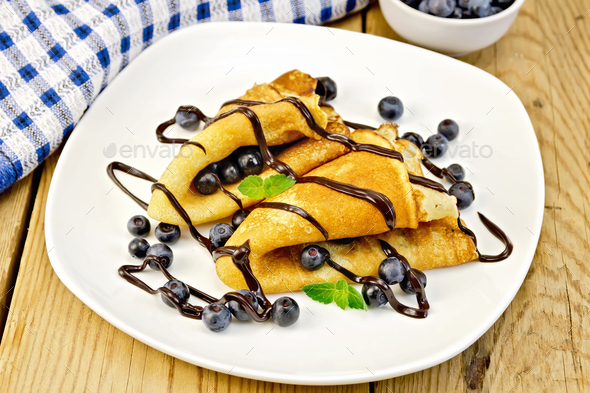 Pancakes with blueberries and chocolate on board - Stock Photo - Images