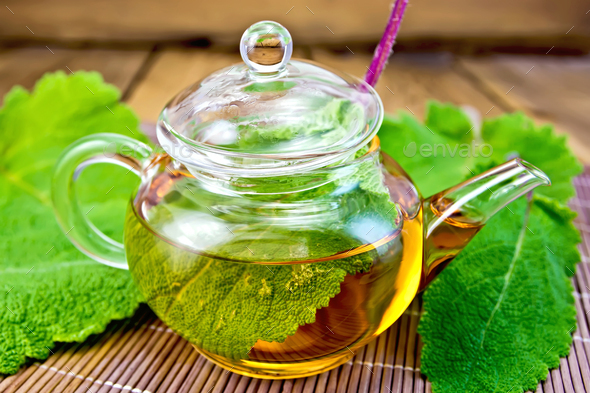 Tea with sage in teapot on bamboo napkin - Stock Photo - Images