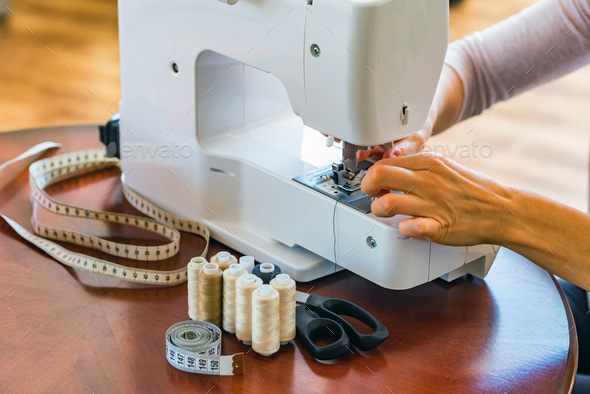 Dressmaker or seamstress works using sewing machine - Stock Photo - Images