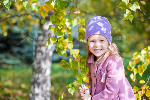 Adorable little girl at beautiful autumn day outdoors - Stock Photo - Images