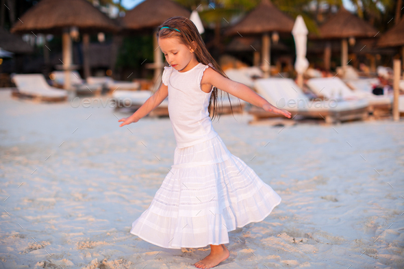 Adorable little girl have fun at sunset beach - Stock Photo - Images
