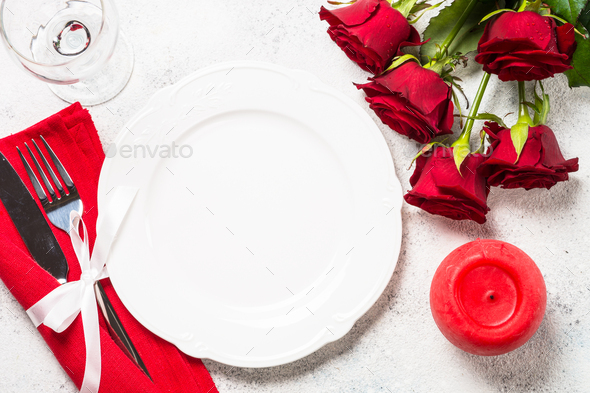Romantic holiday table setting with plate, roses and present - Stock Photo - Images