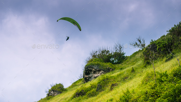Paraglider flying off the Grassy Hills above Gunung Payung Beach, Bali - Stock Photo - Images