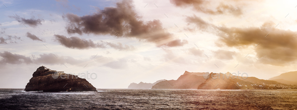 Rocky Atlantic shoreline under dramatic cloudscape. Sunrise on Cape Verde. View from the sea - Stock Photo - Images