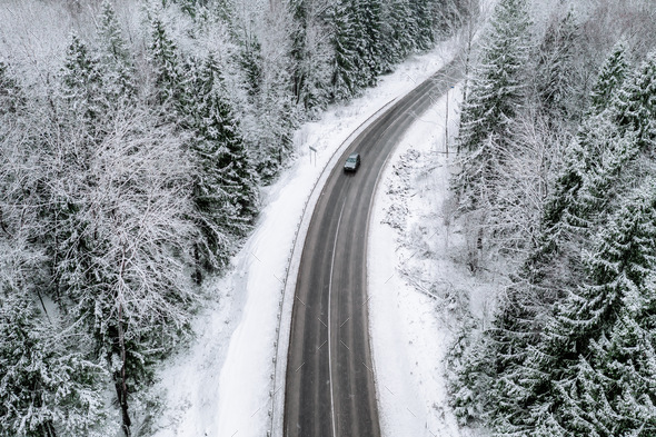 Aerial view of winter road with a car and snow covered forest in Finland - Stock Photo - Images