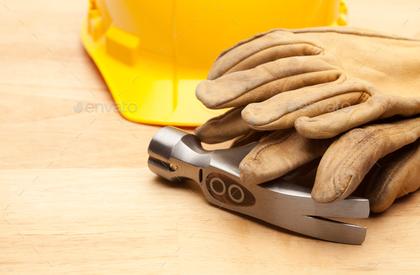 Yellow Hard Hat, Gloves and Hammer on Wood - Stock Photo - Images