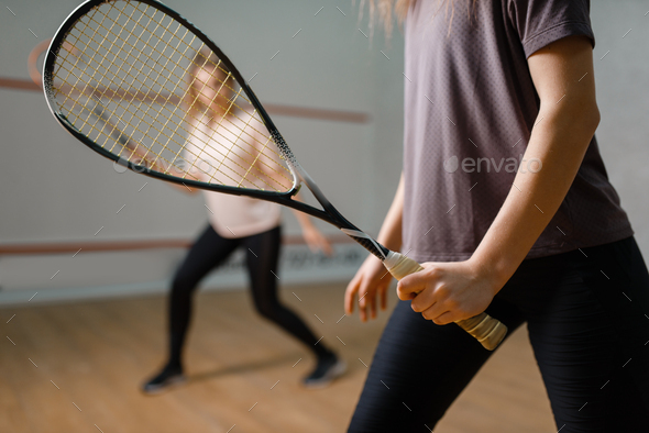 Two female players with rackets, squash game - Stock Photo - Images