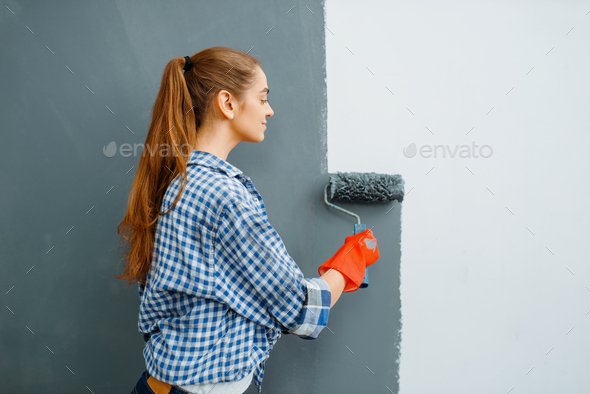 Cheerful female house painter paints walls indoor - Stock Photo - Images