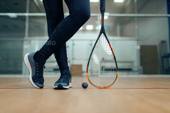 Female player legs, squash racket and ball - Stock Photo - Images