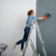 Female house painter in gloves paints the wall - PhotoDune Item for Sale