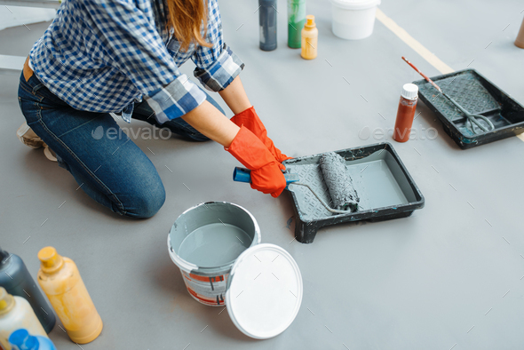 House painter impregnates the roller with paint - Stock Photo - Images
