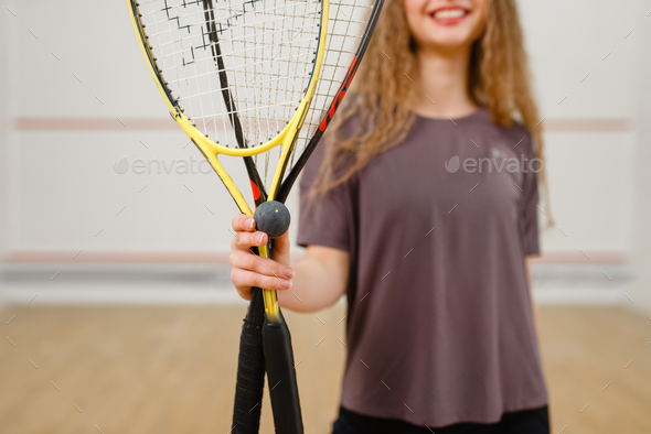Female person shows squash racket and ball - Stock Photo - Images