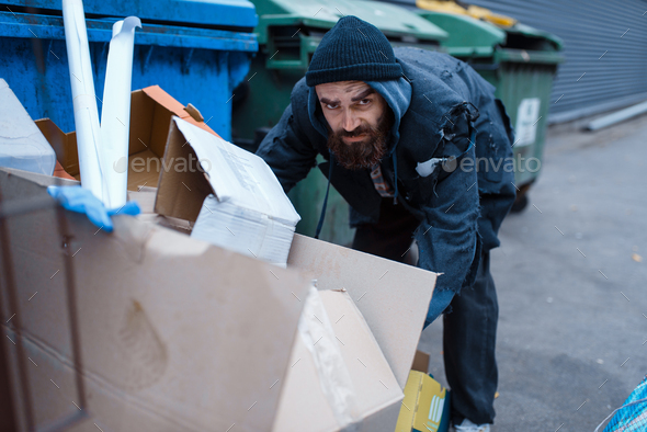 Bearded homeless searching food in trashcan - Stock Photo - Images