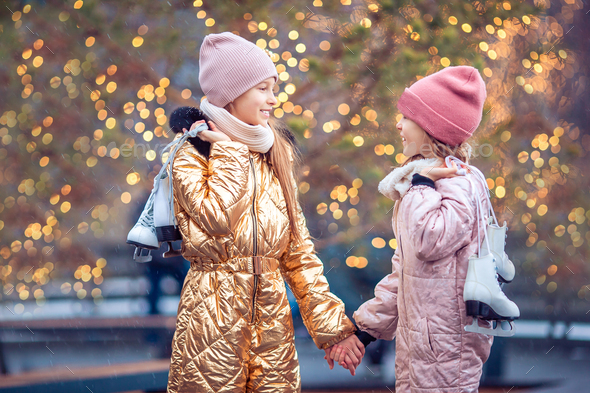 Adorable girls skating on ice rink outdoors in winter snow day - Stock Photo - Images