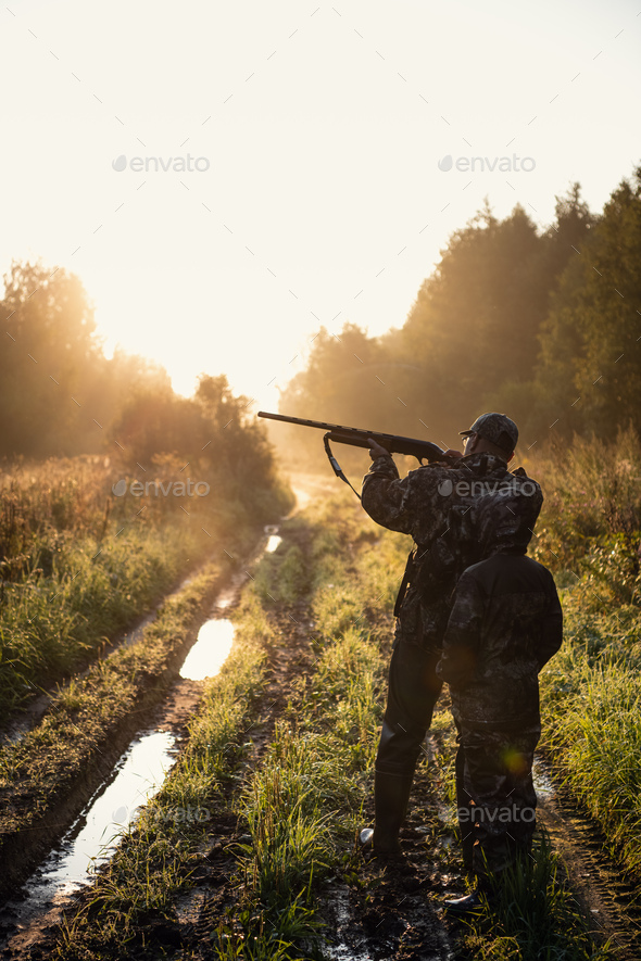 Rifle Hunter and His Son Silhouetted in Beautiful Sunset. Huntsman with a boy and rifle in a forest - Stock Photo - Images